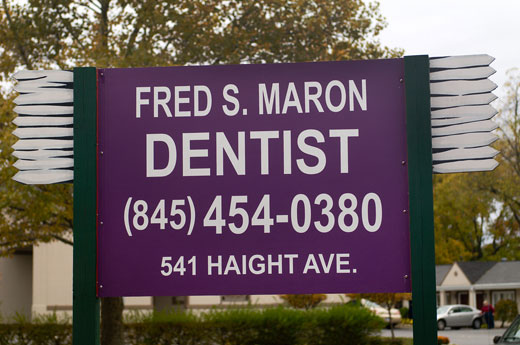 Large sign with toothbrushes for Dr. Maron's dental office at the junction of routes 44 and 55
